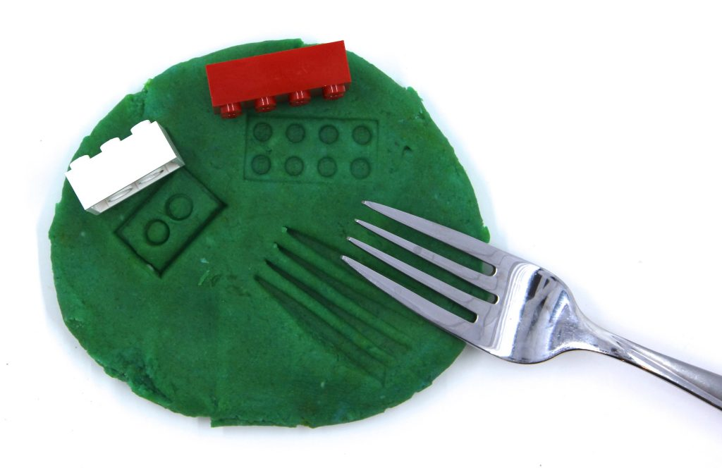 Photo of play dough with impressions from a fork and from Lego bricks.