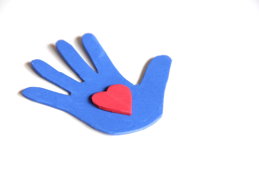 Photo of a blue hand-shape cut from craft foam with a red foam heart on top.
