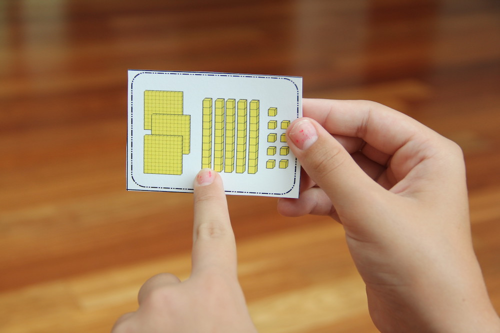 Photo of a child holding a cards that shows 359 represented with yellow base ten blocks. The card is used for the game Base Ten War.