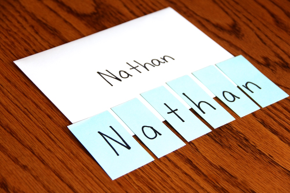 "Photo of a name puzzle. Child's name is written on an envelope. Small blue pieces of paper contain one letter each. When put together they spell ""Nathan."""