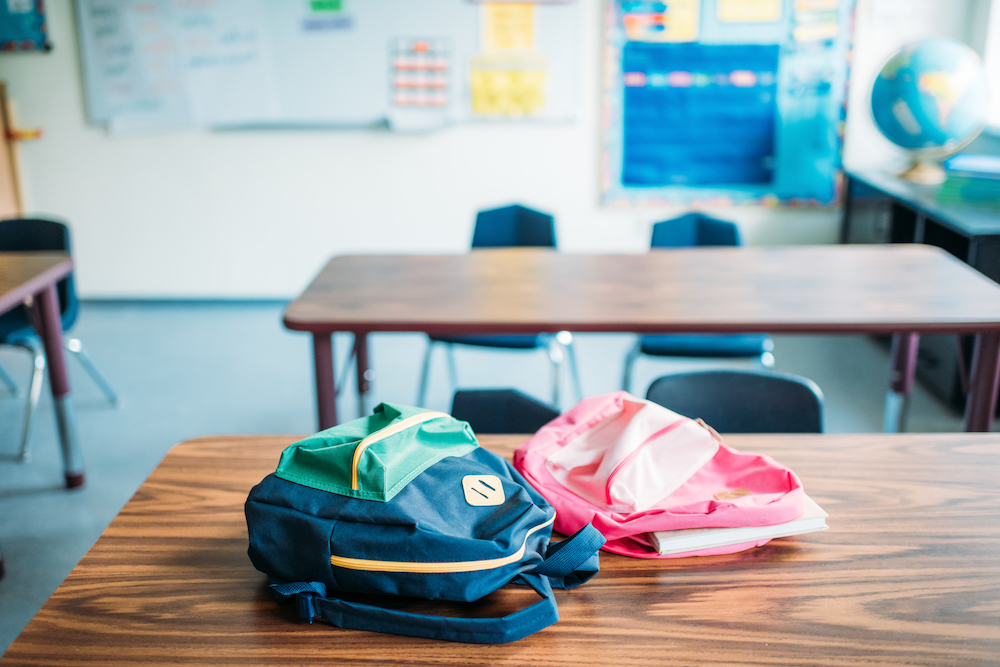 Two backpacks laying on a table in an elementary classroom.