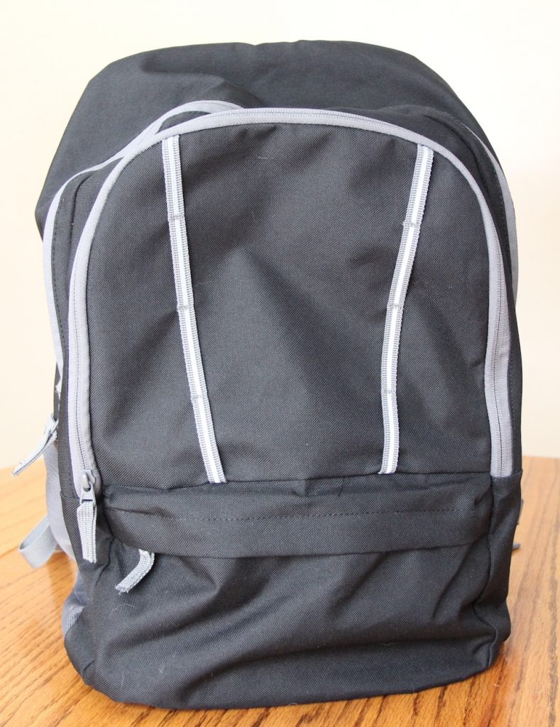 Black backpack zipped up and ready to go home, sitting on a table.
