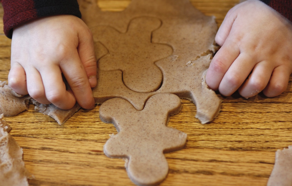 Picture of a child cutting out gingerbread shapes from play dough in a pretend bakery.