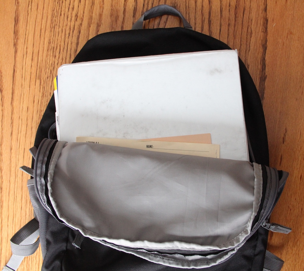 Backpack laying open with binder and papers tucked neatly inside.