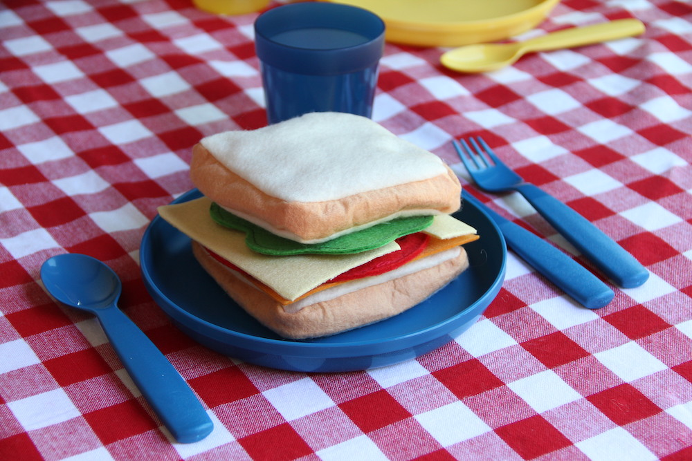 Photo of a pretend sandwich on a blue plate. The plate is on a red checkered table cloth in a dramatic play center kitchen.