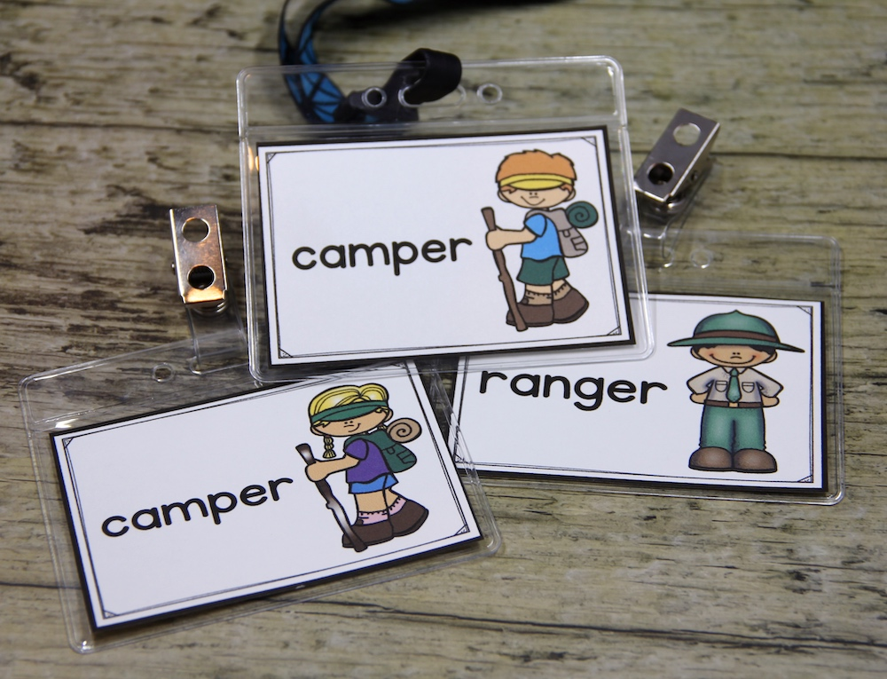 """Photo of student role play badges for a camping center: some say """"camper"""" and one says """"ranger"""""""