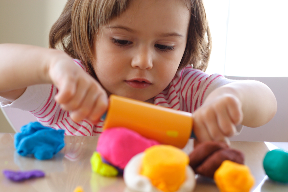 Photo of young girl playing with play dough.