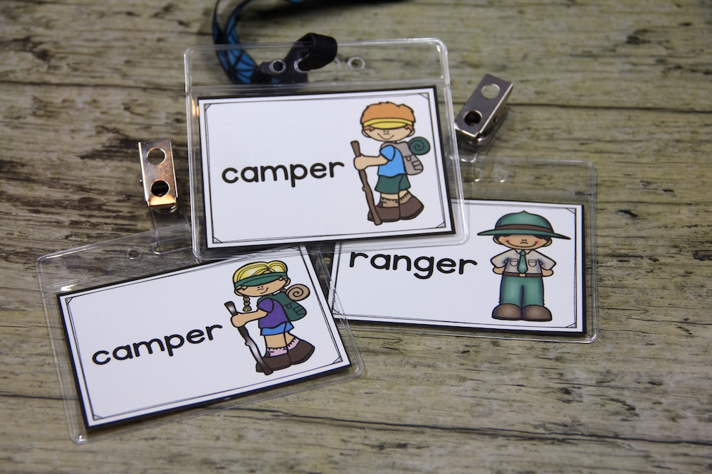 Photo of 3 name badges for students playing in a dramatic play center. These badges have roles for campers and ranger in a camping themed center.