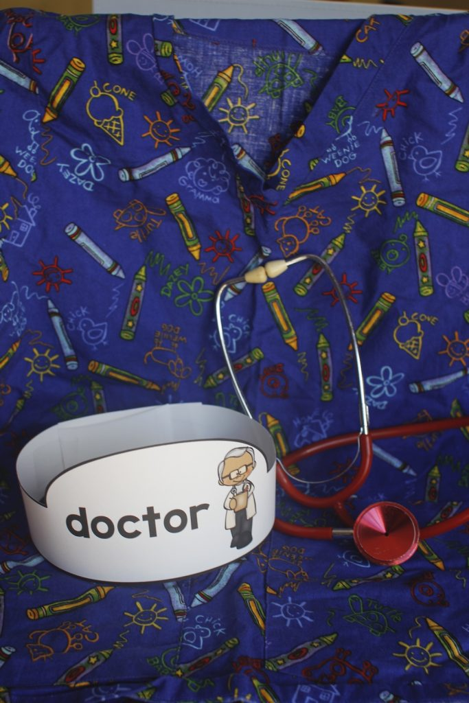 """Photo of a medical scrub shirt, a stethoscope and a paper hat labeled """"doctor"""""""