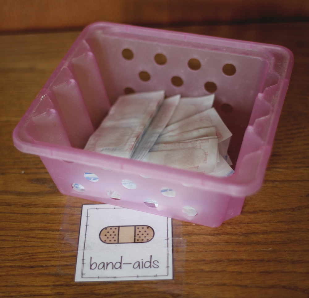 """Photo of a small box containing band-aids on a shelf with a label that says """"band-aids"""" and a drawing of a bandage."""