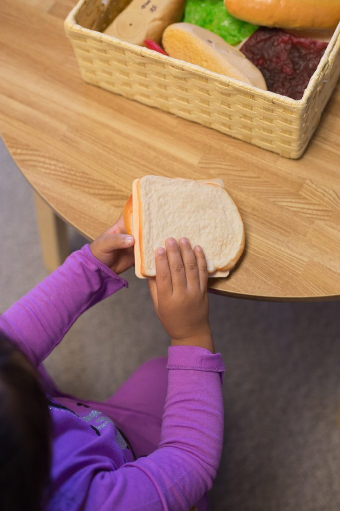 Photo of a young girls holding a pretend sandwich. In the background is a wicker basket holding pretend food.