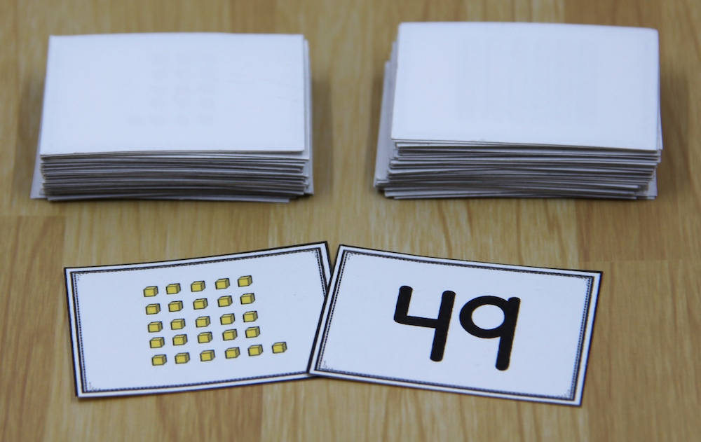 """Photo of two game cards for a math war game. One card shows 26 """"ones"""" cubes; the other shows the number 49."""