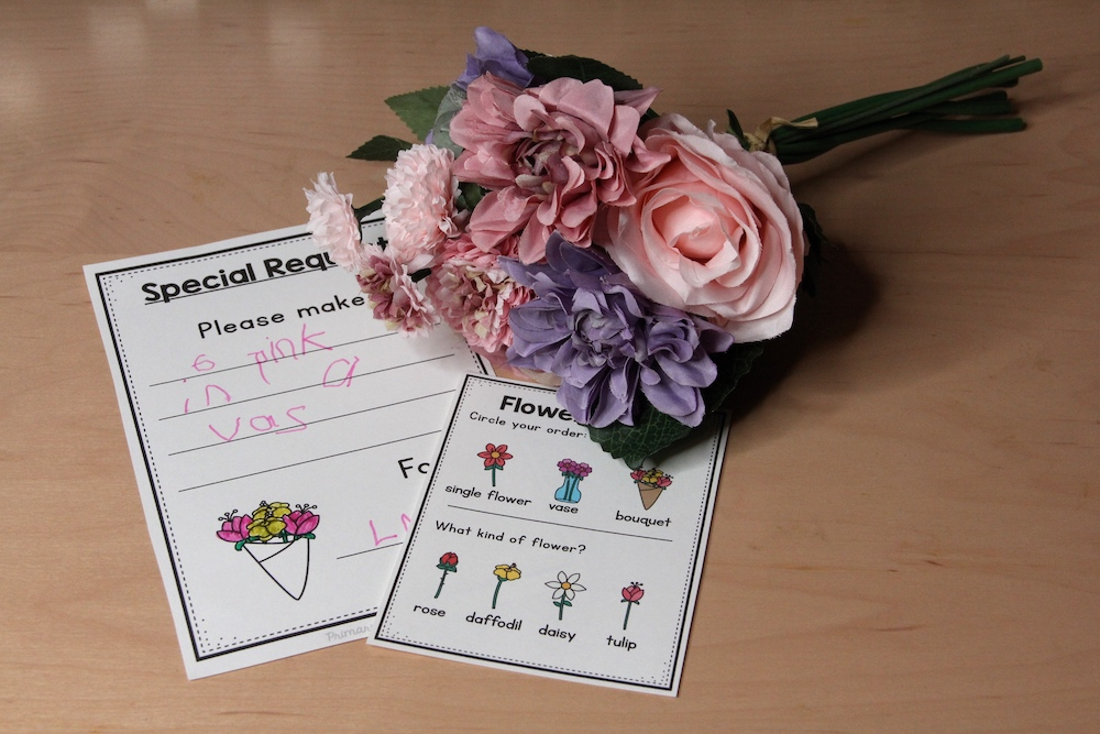 Photo of plastic flowers and orders slips for a pretend flower shop.