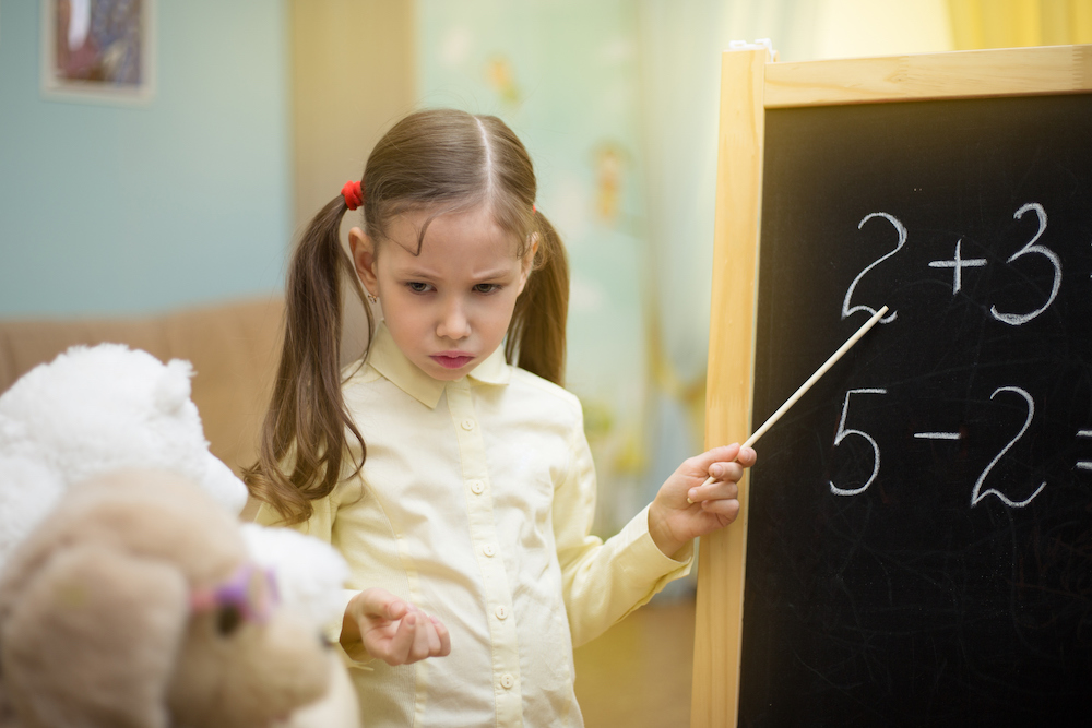 Photo of a young girl pretending to teach her stuffed animals how to add.