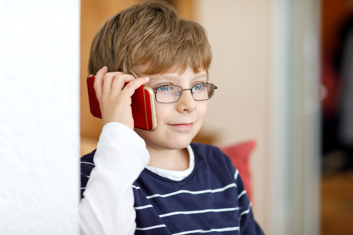 A photo of a young boy in glasses holding a red cell phone to his ear.