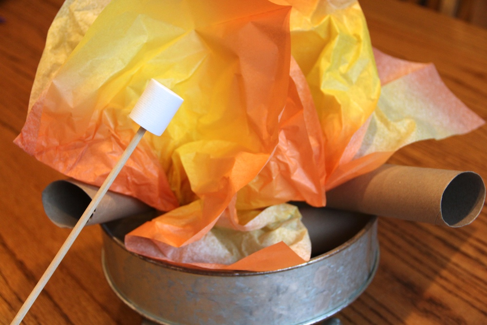 Photo of a pretend campfire with orange and yellow tissue paper for flames. Paper towel tubes are used as logs. A campsite is a great summer dramatic play idea.