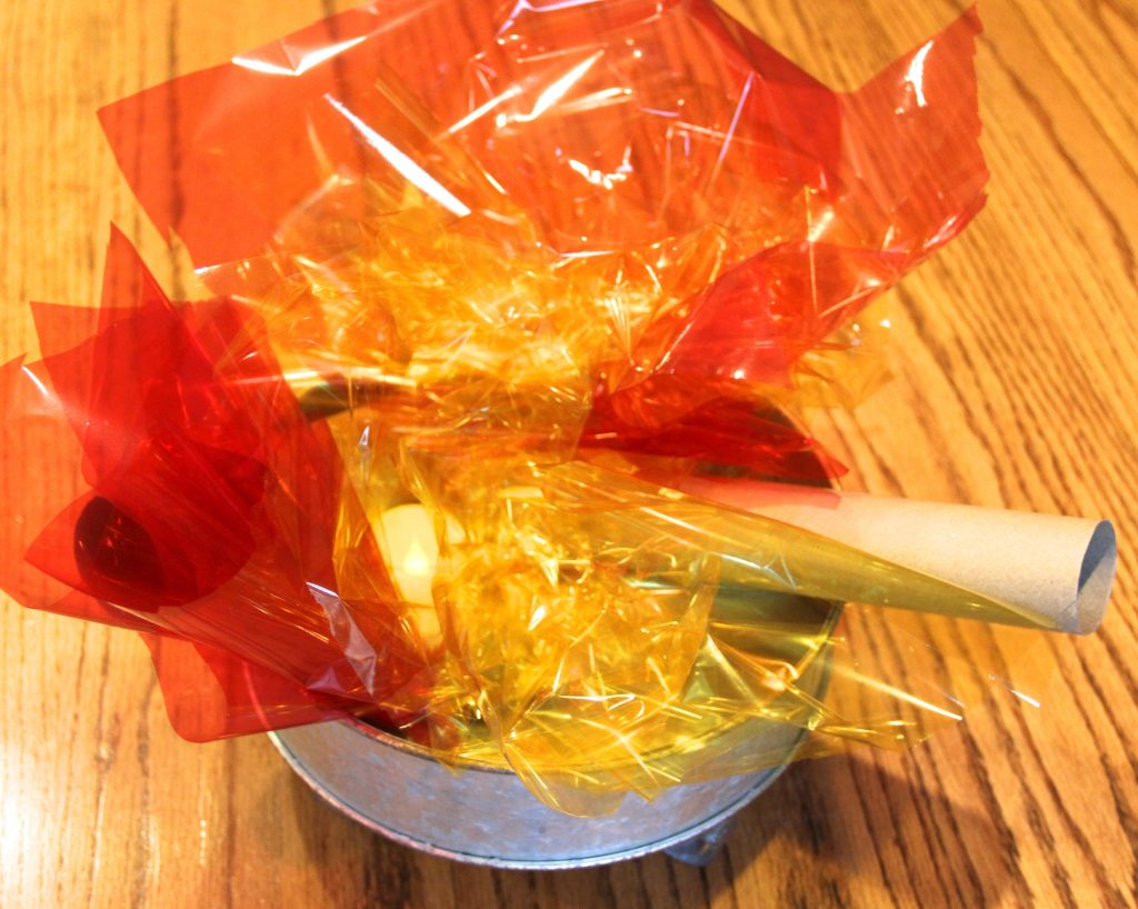 Photo of a pretend campfire in a fall dramatic play center. The fire is made with red, yellow and orange cellophane with paper towel tubes for logs.