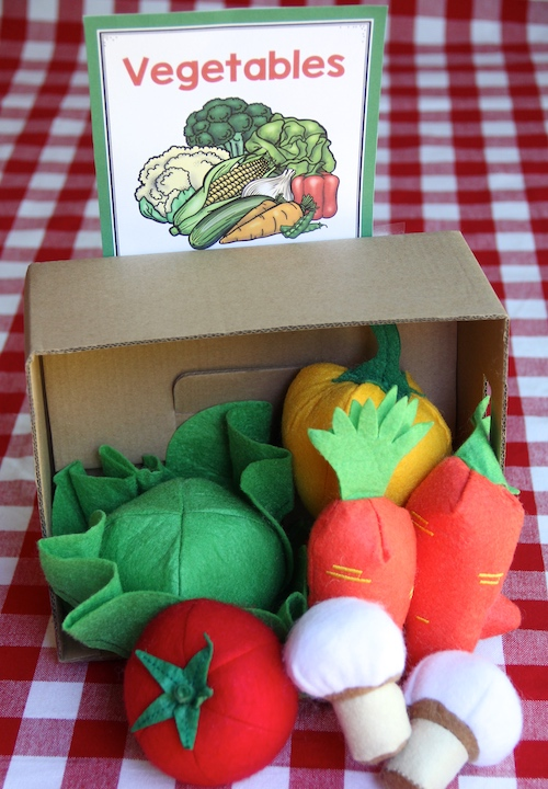 """Photo of fabric vegetables in a box with a sign saying """"Vegetables."""""""