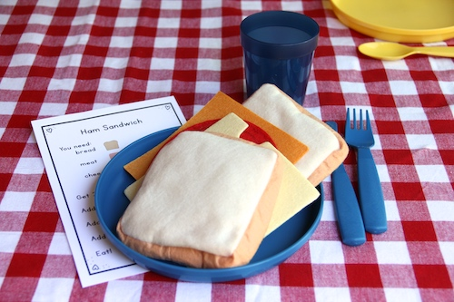 Photo of a scene from a dramatic play kitchen: a pretend sandwich is on a plate, which is on a red-checked table cloth.