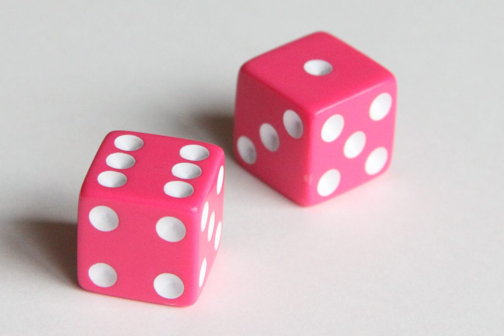 Photo of two pink dice that can be used for many different math games for kids.