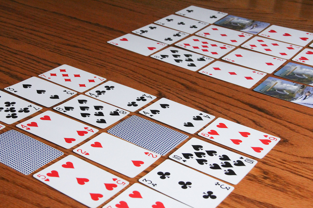 Photos of playing cards arranged in a 4X4 grid to create a homemade Bingo card. Some cards have been turned face down (because those numbers were called).