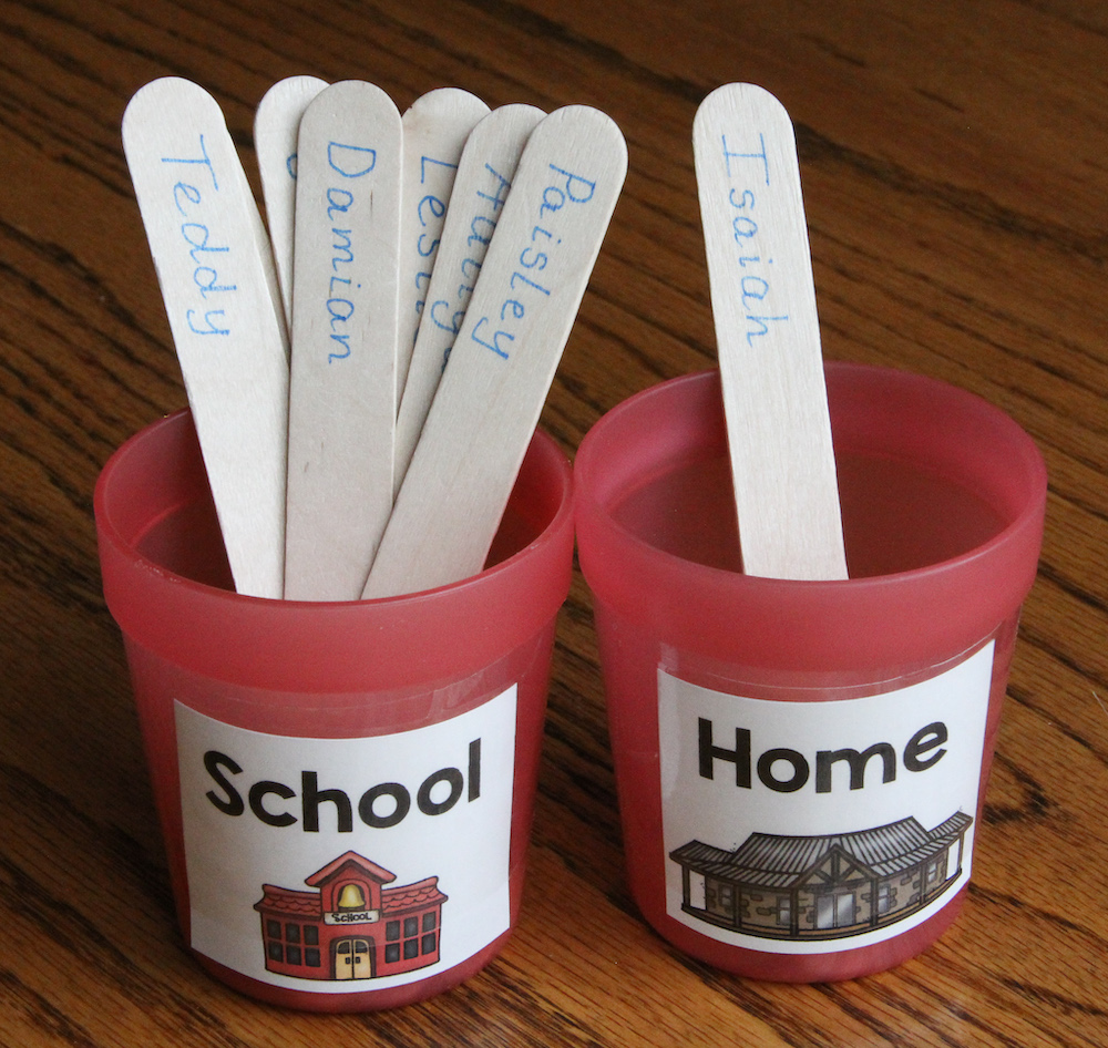 """Photo of two red cups, labeled """"Home"""" and """"School."""" Student name sticks are placed in the cups to indicate attendance."""