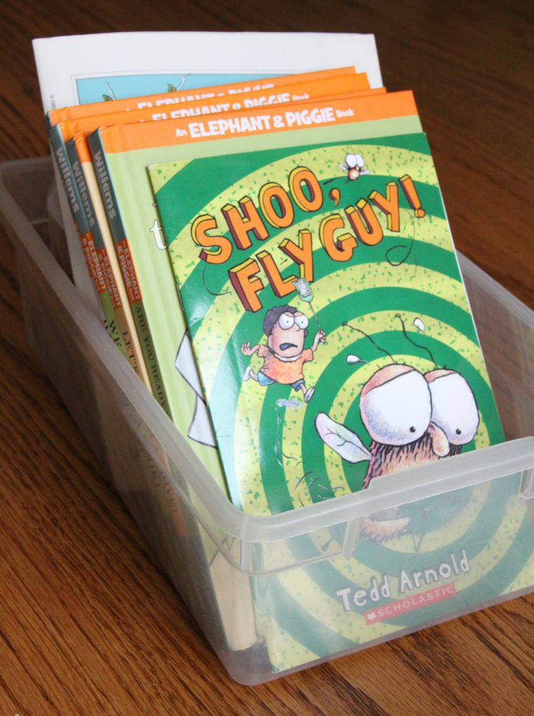 Photo of picture books in a clear plastic storage box.