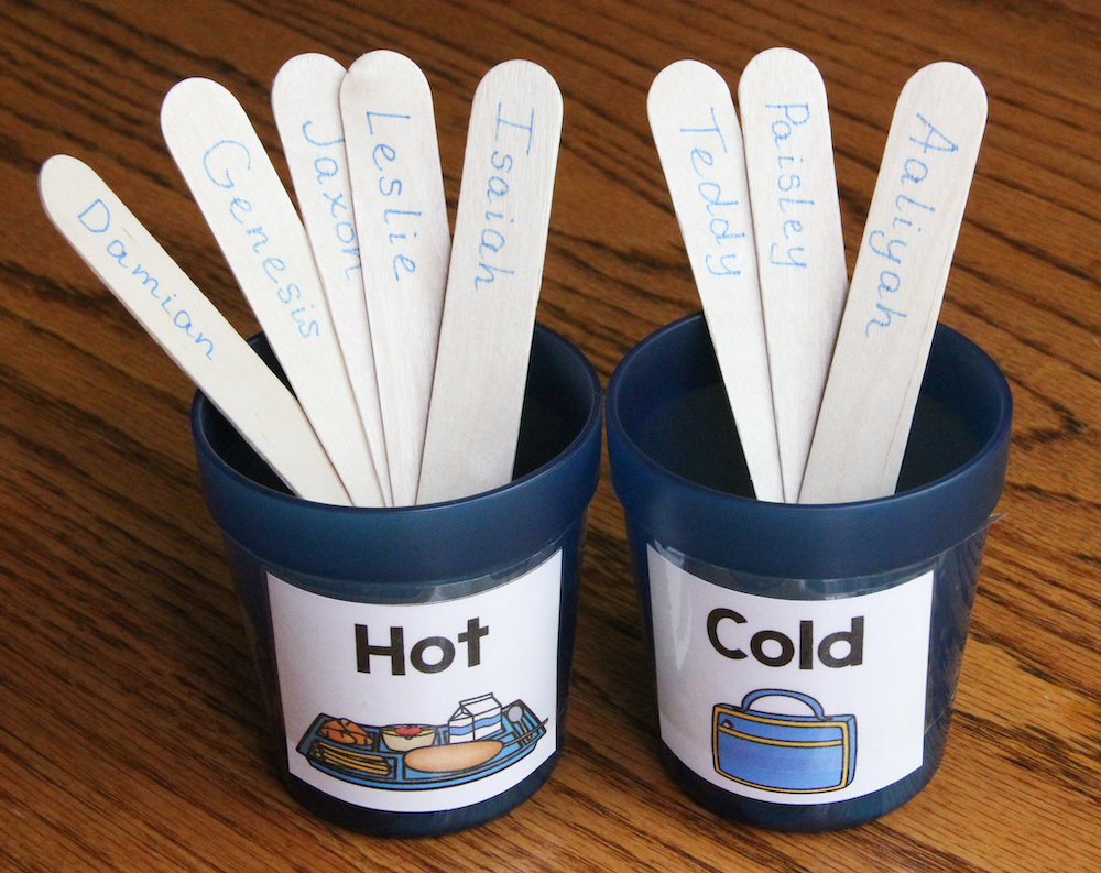 """Photo of two blue cups, labeled """"Hot"""" and """"Cold."""" Student name sticks are placed in the cups to indicate lunch choices."""