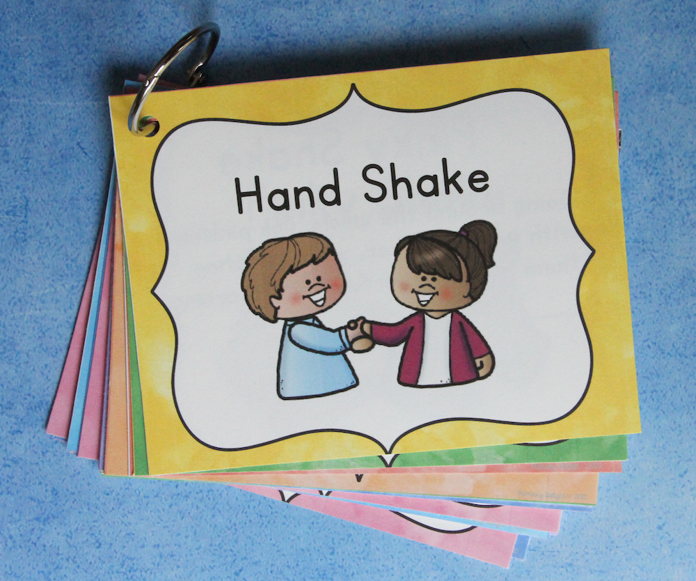 """Photo of morning meeting greeting cards on a ring. Top card says """"Hand Shake"""" and shows two students shaking hands."""