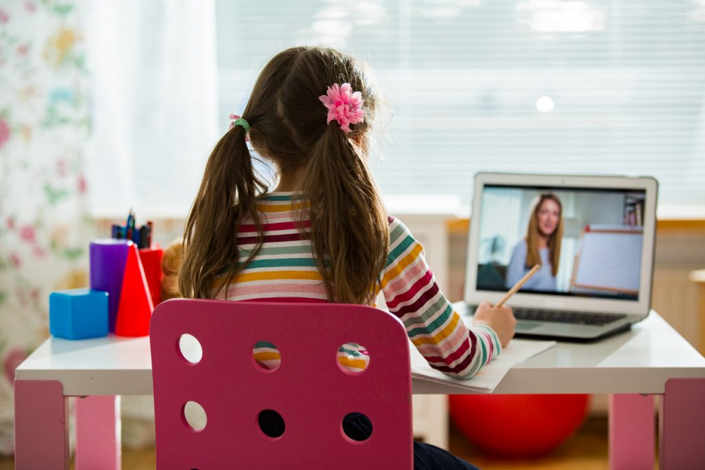 Photo of you girl sitting at a desk at home - engaged in a distance learning reading lesson. She faces a computer that shows a teacher standing in front of an easel.
