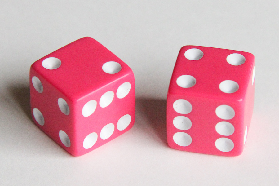 A photo showing two pink dice, showing the numbers 2 and 4.