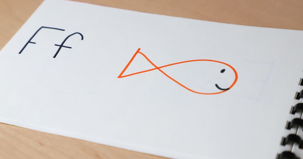 Photo of one student's personalized alphabet book. The page shows the letter Ff and a quick drawing of a fish.