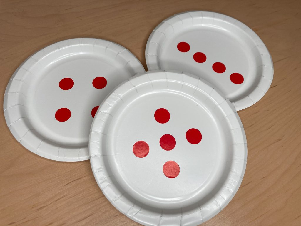 Photo of paper plates with dots arranged to show 4 (2 groups of 2 and a line of 4) and 5.