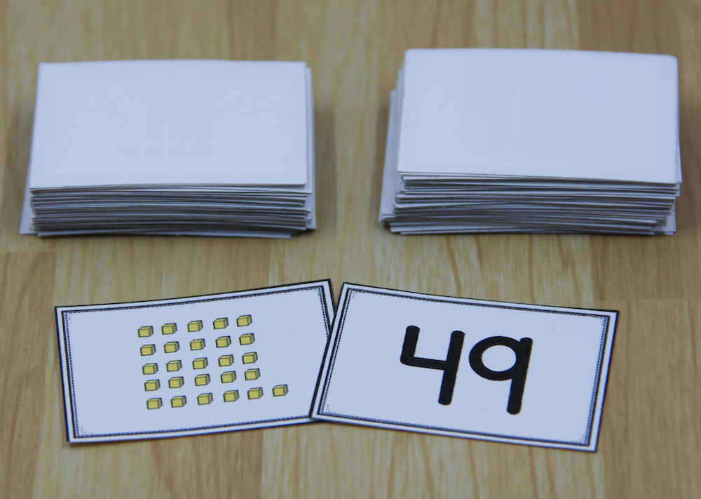 """Photo of two place value war cards - one showing the numeral 49 and the other showing 26 """"ones"""" cubes."""