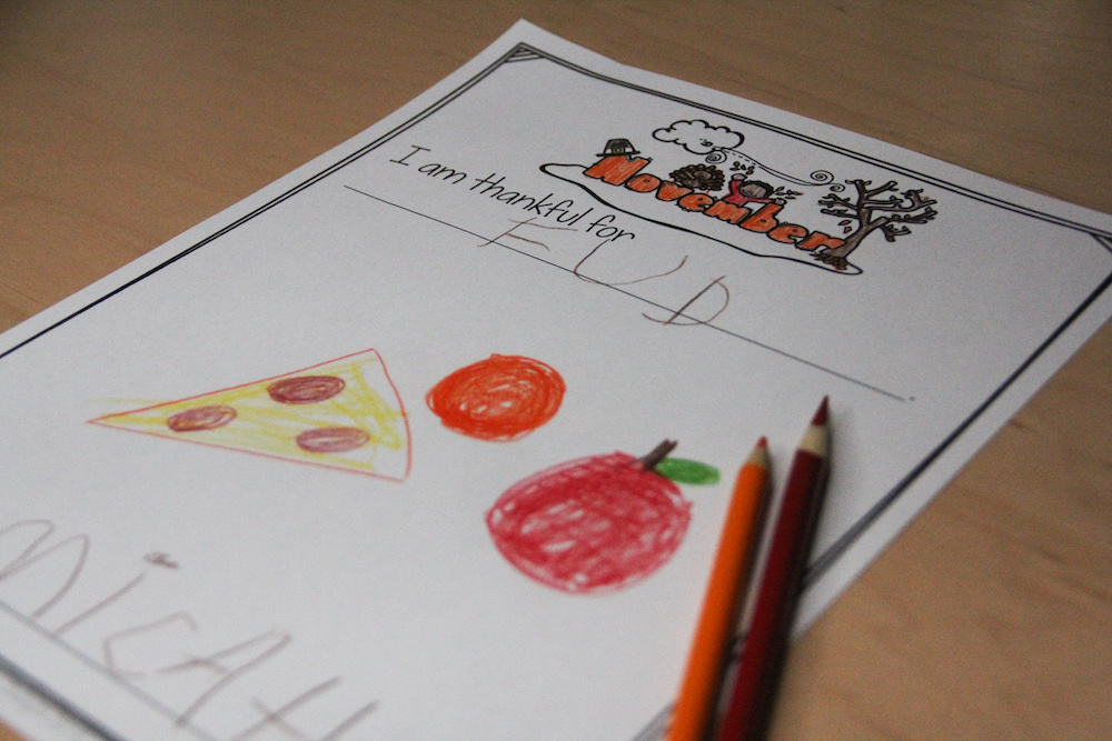 Photo of a portfolio page for parent teacher conferences. Child drew food following a prompt about what he was thankful for.