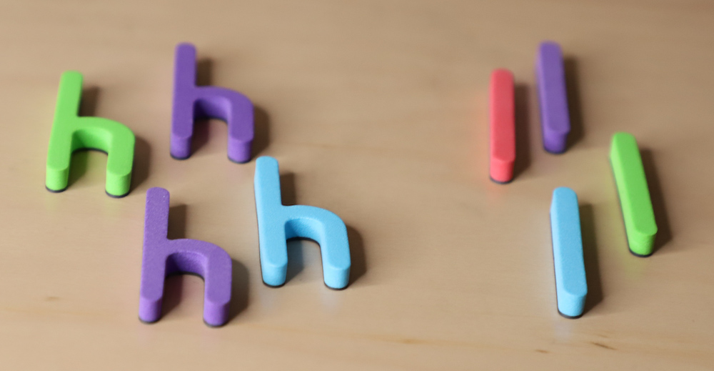 Photo of colorful letter magnets that are sorted by letter (h and l.)