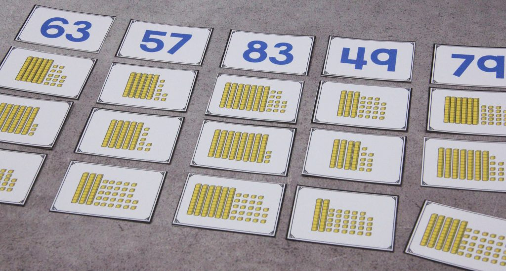 Photo shows cards with yellow place value blocks sorted by the numeral they represent. Some cards have more than ten ones-blocks.