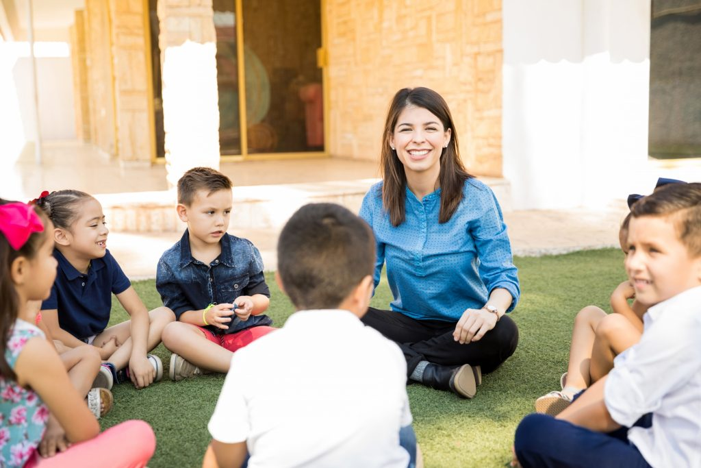 Photo of a teacher is sitting in a circle outside with students, playing morning meeting games.